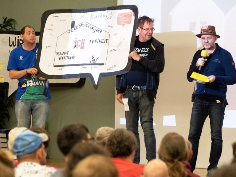 Bild von der Fach-Tagung Essen - 3 Männer halten Präsentation